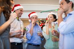People in Santas hats with champagne flutes and noise makers - stock photo