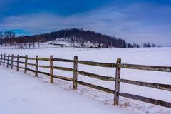 Fence and snow covered farm fields in rural adam's county, pennsylvania. Stock Photos