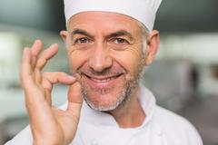 Happy chef looking at the camera making ok sign Stock Photos