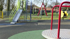 A round about spinning to a stop at an empty playground Stock Footage