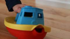 Boy playing with toy boat Stock Footage