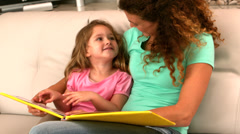 Mother and daughter reading book on the couch - stock footage