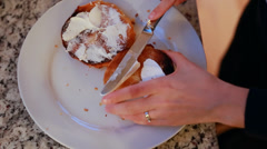 A woman spreading cream cheese on a bagel Stock Footage