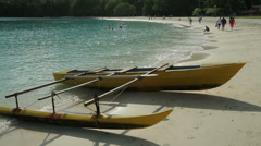 Outrigger canoe on tropical beach with tourists, champagne bay, vanuatu Stock Footage
