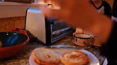 A woman putting bagels in toaster oven Stock Footage