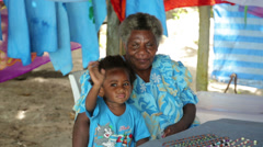 Local woman and child look at camera champagne bay, vanuatu Stock Footage