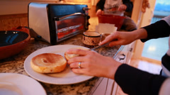 Woman putting cream cheese on toasted bagel Stock Footage