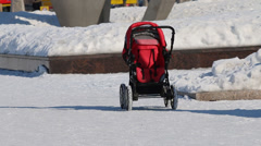 Mother with her kid coming to a rolling red stroller - stock footage