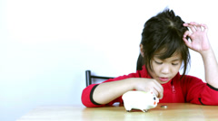 Cute Asian girl save money in piggy bank Stock Footage