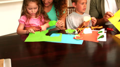 Parents and children making paper shapes together at the table - stock footage