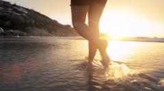 Woman walking on beach barefoot sunset steadicam shot Stock Footage