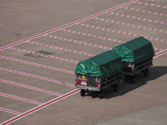 tractors and dollies carrying luggage on dusseldorf airport apron. - stock footage