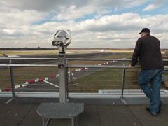 People watching airplanes on dusseldorf airport coin binoculars Stock Footage