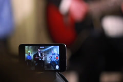 Shooting video of performance using phone, music band plays, click for HD Stock Footage