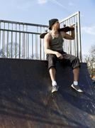 Portrait of a skateboarder sitting on top of a half pipe ramp - stock photo