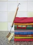 Stack of kitchen towels with dish-washing brush Stock Photos