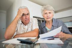 Worried couple paying their bills looking at camera Stock Photos