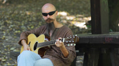 Guitarist plays guitar in park Stock Footage