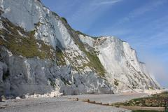White cliff, partly covered with green vegetation, against a blue sky. - stock photo