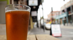 Glass pint of Pale Ale beer outdoors with city street in background Stock Footage