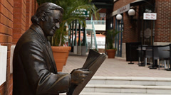 Statue of man reading newspaper in Historic Ybor City florida Stock Footage