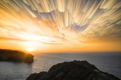 Unique abstract time lapse stack sunrise landscape over rocky coastline Stock Photos