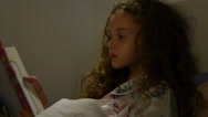 Stock Video Footage of Little girl reading a book on bed at night. Professionally lighted.