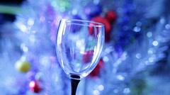 Glass filled with red vine in front of Christmas tree Stock Footage