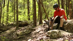 Mountain biker looking at a bent rim Stock Footage