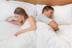 Couple not talking after an argument in bed Stock Photos