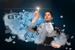 Asian businessman pointing to light above app cloud Piirros