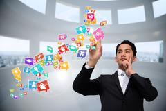 Asian businessman pointing to app icons Stock Illustration