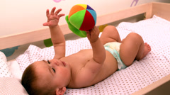 Baby lying in crib holding toy Stock Footage