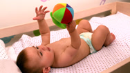 Stock Video Footage of Baby lying in crib holding toy