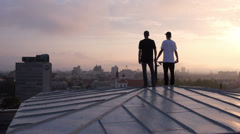 AERIAL: Two young skateboarders standing on rooftop Stock Footage