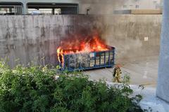Fire Fighter Preparing To Extinguish A Fire Burning In A Commercial Dumpster - stock photo