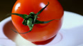 Tomato turns on a white plate close up HD Footage