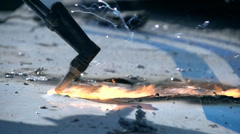 Burner cutting iron in slow motion, fire and small sparks move slowly Stock Footage