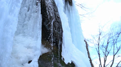 Water runs down the frozen waterfall in slow motion Stock Footage
