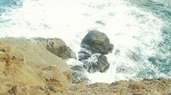 Waves break on a huge rock-ness. View from above. Rapid. Stock Footage