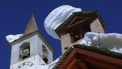 Church tower with snowy roof against blue sky Stock Footage