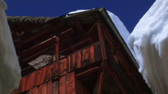 Wooden house with snowy stone roof against blue sky Stock Footage
