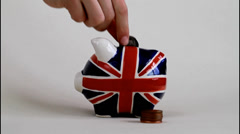 British Piggy Bank. three coins being placed in it. Stock Footage