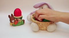 Hand putting Easter eggs in bunny basket decoration, bunny egg holder - stock footage
