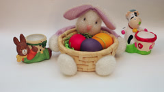 Hand putting Easter eggs in bunny egg holders, bunny basket decoration - stock footage