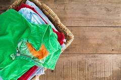 clean unironed summer clothes in a laundry basket - stock photo