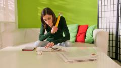 Young woman studying at home with big pencil Stock Footage