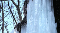 Small waterfall runs down the icicles background blue sky and trees Stock Footage