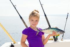 blond girl fishing bonito sarda tuna trolling in sea - stock photo