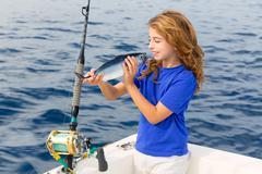 blond girl fishing bluefin tuna trolling in mediterranean - stock photo